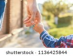 the parent holding the child's... | Shutterstock . vector #1136425844