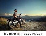 biker leaning on a motorcycle... | Shutterstock . vector #1136447294