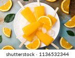 orange popsicles with juice on... | Shutterstock . vector #1136532344
