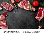 meat raw steaks lie on a black... | Shutterstock . vector #1136733584