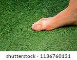 foot on plastic grass background   Shutterstock . vector #1136760131