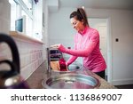 mid adult woman is filling her... | Shutterstock . vector #1136869007