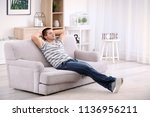 young man relaxing on sofa at... | Shutterstock . vector #1136956211