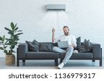 handsome man turning on air... | Shutterstock . vector #1136979317