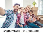 Small photo of Self portrait of young happy smiling family four persons sitting on floor near carton boxes packages with stuff things in light living room, moving to new flat, showing v-sign gesture