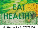 "Small photo of ""EAT HEALTHY"" diet motivational message written in big letters over real picture of vegetables, green design for poster or sign about weight loss motivation. Inspirational quote."