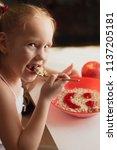 little girl eating appetizingly ... | Shutterstock . vector #1137205181