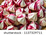 Small photo of Modern fashion trend : fruit meringues. Colorful, striped meringue kisses flavored with seedless raspberry jam.