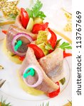 appetizer with rolled herring fillet stuffed with red pepper and gherkin on potato ring for christmas - stock photo