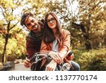 young couple sitting on bicycle ... | Shutterstock . vector #1137770174