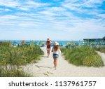 Girls Walking On The Beach On...