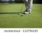 golfer taps in a putt on a green | Shutterstock . vector #113796235