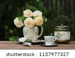 Stock photo gorgeous bouquet of fresh roses in old antique faience ceramic porcelain pitcher floral pattern 1137977327