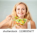 young woman eating vegetable... | Shutterstock . vector #1138035677