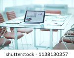 laptop and financial reports on ... | Shutterstock . vector #1138130357
