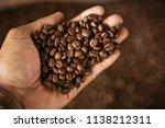 hand holding roast coffee beans. | Shutterstock . vector #1138212311