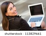Businesswoman working outdoors on a laptop computer - stock photo