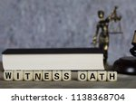 Small photo of Word WITNESS OATH composed of wooden letters. Statue of Themis,judge's gavel, bible in the background