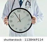 doctor holding wall clock...   Shutterstock . vector #1138469114