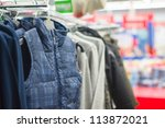 Vests and jackets on stands in supermarket - stock photo