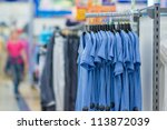 Color T-shirts on stands in supermarket - stock photo