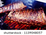pork ribs on the grill cooking... | Shutterstock . vector #1139048057