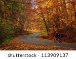 Man riding a bike on a curved road in autumn scenary / Autumn bike riding - stock photo