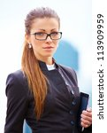 Businesswoman working with digital tablet looking at camera over building background - stock photo