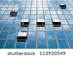 Office windows on the glass buildings with clouds reflecting - stock photo