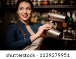 Stock photo attractive bartender girl in the white apron holding in her hands two steel cocktail shakers at the 1139279951