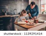 father preparing breakfast for... | Shutterstock . vector #1139291414
