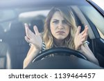 Small photo of Angry woman driving a car. The girl with an expression of displeasure is actively gesticulating behind the wheel of the car.