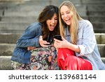 two young women looking at some ... | Shutterstock . vector #1139681144
