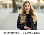 blonde woman texting with her... | Shutterstock . vector #1139681507