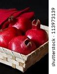 Fresh pomegranates in a wicker box on a black. - stock photo