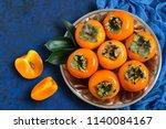 ripe persimmon on metal plate...   Shutterstock . vector #1140084167