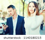 Small photo of Young couple strolling together and ignoring each other speaking on phones