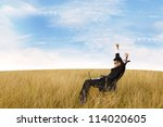 Free successful businessman with laptop in the field - stock photo