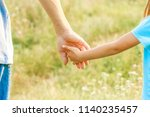 hands of parent and child in... | Shutterstock . vector #1140235457