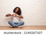 Young Black Woman Sitting On A...
