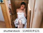 woman sitting in sauna room in... | Shutterstock . vector #1140319121