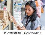 asian woman chooses thanakha at ... | Shutterstock . vector #1140406844