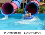 young man ride on a slide in a... | Shutterstock . vector #1140493907