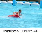 young man ride on a slide in a... | Shutterstock . vector #1140493937