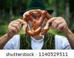 bavarian man holding a pretzel... | Shutterstock . vector #1140529511