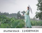 Asian woman dressed in costume Hanfu playing in the lotus garden.