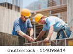 Construction workers collaborating in the installation of cement formwork frames - stock photo