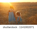 young girls joys on the wheat... | Shutterstock . vector #1141002071