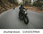 man riding a black classic... | Shutterstock . vector #1141015964