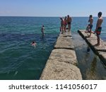 children jumping into the sea... | Shutterstock . vector #1141056017